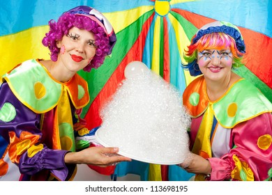 Clowns are making fun on colorful background