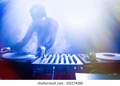 Club DJ playing mixing music on vinyl turntable at party from nightlife lights.