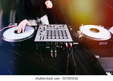 Club DJ playing mixing music on vinyl turntable at party from nightlife lights