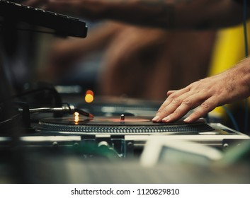 Club dj scratch vinyl records with music on hip hop party in club.Professional disc jockey mix musical tracks with turntables player and sound mixer on concert in the nightclub