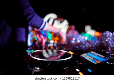 Club party dj plays live set on stage in nightclub.Professional disc jockey mix popular musical tracks with vintage turnables & vinyl records