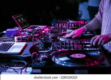 Club party dj plays music with turntables.Hands of hip hop disc jockey man scratching vinyl records on stage in nightclub.Professional audio equipment on scene.Retro turn table player and sound mixer