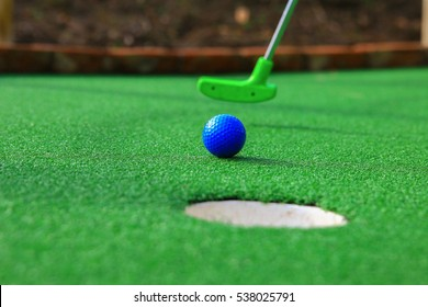 A club prepares to hit a ball during a mini golf game
