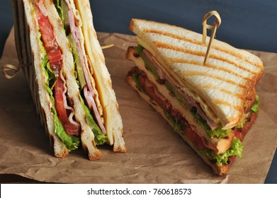 Club sandwich with bacon and ham on kraft paper. The sandwich is divided in half into two triangles. The sandwich is made from white bread, fried on a grill. Close-up. Macro photography.