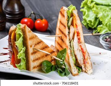 Club sandwich with cheese, cucumber, tomato, chicken meat and lettuce on dark wooden table. Delicious snacks, sandwiches, antipasti