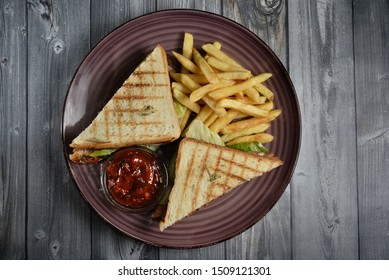 Club Sandwich with Cheese, PIckled Cucmber, Tomato and Smoked Meat. Garnished with French Fries on wooden table