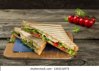 Club sandwich with chicken breast, tomato, cheese and green salad on the wooden background