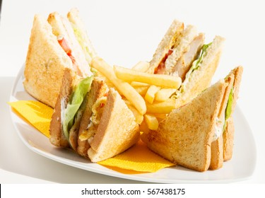 Club Sandwich with fries on sunshine, arranged and split