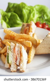 Club sandwich with grilled chicken, tomato, lettuce, cheese, cucumber and dressing sauce, served on a white plate with french fries.