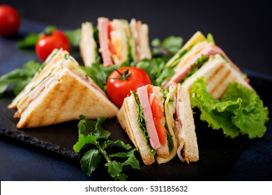 Club sandwich with ham, bacon, tomato, cucumber, cheese, eggs and herbs on dark background.