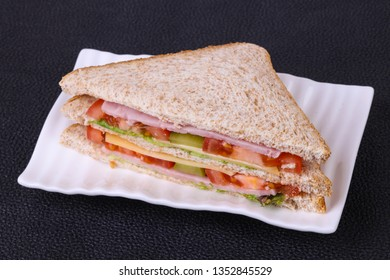 Club sandwich with ham , cheese, salad leaves, tomatoes and pickled cucumbers
