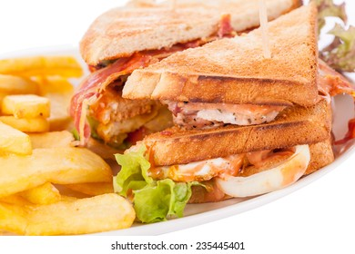 Club sandwich on toasted white bread with a meat filling served with crispy golden potato French fries, closeup partial view isolated on white