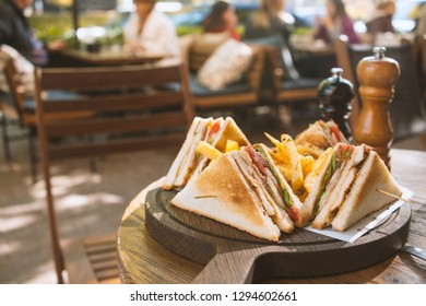 Club sandwich on wooden board on a table in a cafe