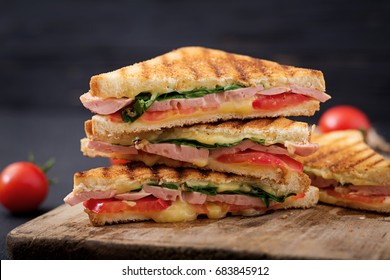 Club sandwich panini with ham, tomato, cheese and basil