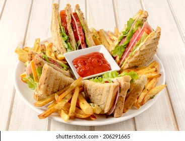 Club sandwiches and french fries in the plate on wooden background