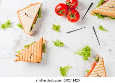 Club sandwiches with fresh lettuce, tomato, cucumber and salmon (trout). On crunchy toast. With ingredients on white concrete stone table top view copy space