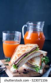 club sandwiches with orange juice on wood background