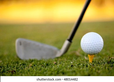 club and white golf ball over grass outdoors