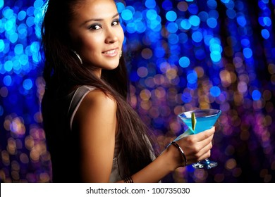 Clubbing girl holding a cocktail and looking at camera with a sensual smile