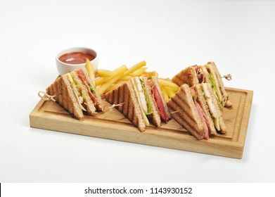 Club-sandwich and french fries on a light wooden board. Next to the potatoes is a cup of ketchup. White background. Close-up.