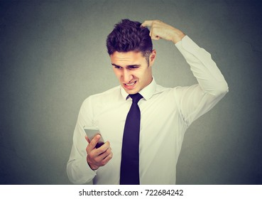 Clueless confused business man having troubles with his smartphone. Complicated technology concept