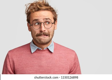 Clueless confused Caucasian male bites lower lip and looks with anxious expression aside, worries before something important in life, make decision, dressed casually, isolated over white wall