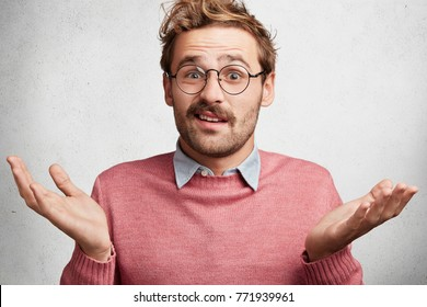 Clueless doubtful male wonk wears round spectacles, shrugs shoulders in bewilderment as doesn`t know answer on question, hesitates, isolated over white concrete background. Body language concept