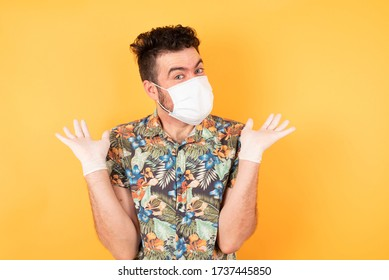Clueless european man, shrugs shoulders with hesitation, faces doubtful situation, spreads palms, wears hawaiian shirt with medical mask and gloves isolated over yellow background. Hard decision
