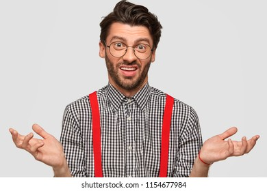 Clueless hesitant male with trendy haircut, wears fashionable outfit and spectacles, shruggs shoulders with uncertainty, makes choice, isolated over white background. People and body language concept