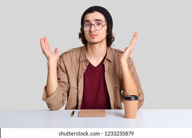 Clueless hesitant youngster spread palms with apathy, looks with puzzlement, wears round optical glasses, hat and shirt, has no ideas what to write, drinks coffee, isolated over white background