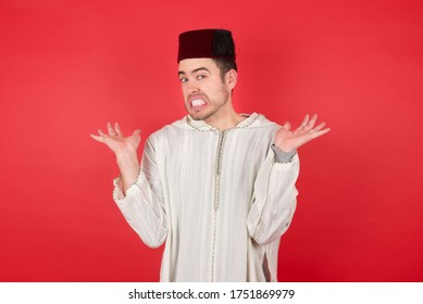 Clueless young caucasian muslim man wearing djellaba and traditional hat over red background, shrugs shoulders with hesitation, faces doubtful situation, spreads palms. Hard decision