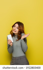 clueless young woman with curly hair holding smartphone and gesturing on yellow