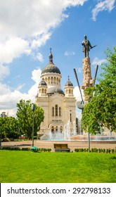 Cluj Napoca Orthodox Cathedral church with the statue of national hero Avram Iancu and fountain in the Square with the same name with fresh green grass and trees and a blue cloudy sky
