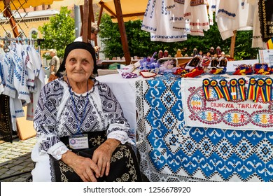 Cluj Napoca, Romania - July 27, 2018: A woman dressed in traditional romanian clothes, selling traditional romanian clothes and souvenirs in a bazaar shop in Cluj Napoca, Romania