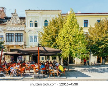 CLUJ NAPOCA, ROMANIA - SEPTEMBER 13, 2018: Tourists Relaxing Downtown In The Old Center Of Cluj Napoca