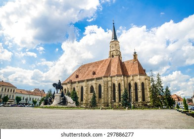 Cluj Napoca Unirii Square with the medieval gothic St Michael Church and the statue of Matei Corvin or Matias Rex on a sunny summer day with a beautiful sky in Transylvania region of Romania