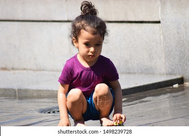 CLUJ, ROMANIA - April 29, 2018: Child playing with the water in the splash of public city fountain sprinkler on a hot day. Kids enjoy the splash on hot sunny day.