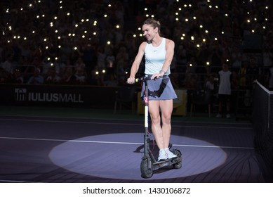 CLUJ, ROMANIA - JUNE 15, 2019: Tennis player legend Simona Halep entering the playground on electric scooter to promote green power energy at Sport Festival