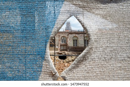 Cluj-Napoca, Cluj / Romania - August 4 2019: On a building site, a hole allows people to see behind the protection where the city is.