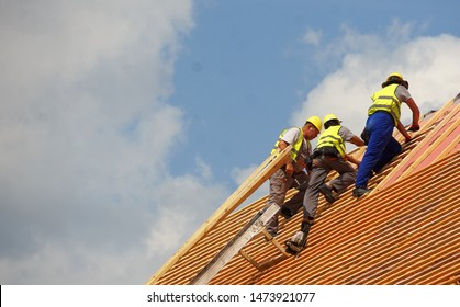 Cluj-Napoca, Cluj / Romania - August 5 2019: Workers are repairing a roof. Above them, a blue cloudy sky.