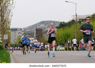CLUJ-NAPOCA, ROMANIA - APRIL 15, 2018: Marathon runners compete at the Wizz Air Cluj-Napoca Marathon. Men and women of all ages run on the streets of the town.