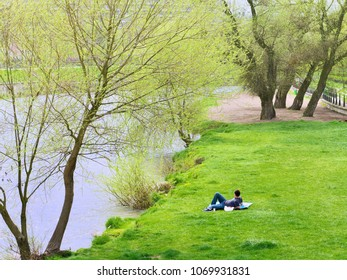 Cluj-Napoca, Romania - April 15, 2018: Young male relaxes on a blanket in the fresh green spring grass near the river.
