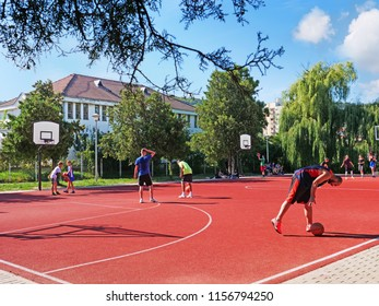 Cluj-Napoca, Romania - August 11, 2018: Happy teenagers and an adult play basketball on a public court outdoors