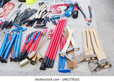 Cluj-Napoca, Romania - August 18, 2019: Various household tools on display at the flea market. Bicycle pumps, scythes, wrecking bars and hatchets for sale lay on a plastic sheet.