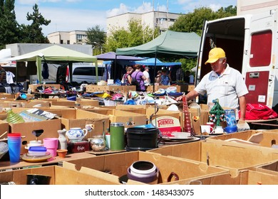 Cluj-Napoca, Romania - August 18, 2019: Man is interested in vintage tableware for sale at the flea market. Secondhand porcelain plates, bowls, cups, glassware and used kitchen utensils on tables.
