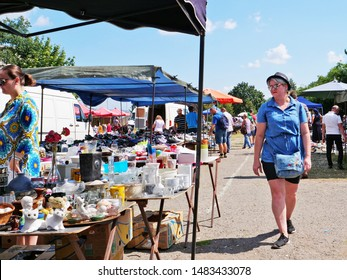 Cluj-Napoca, Romania - August 18, 2019: Woman in shorts and casual outfit approaches a stall with vintage tableware and home decorations at the flea market.