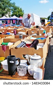 Cluj-Napoca, Romania - August 18, 2019: Vintage tableware for sale at the flea market. Secondhand porcelain plates, bowls, cups, glassware and used kitchen utensils on tables and in boxes.