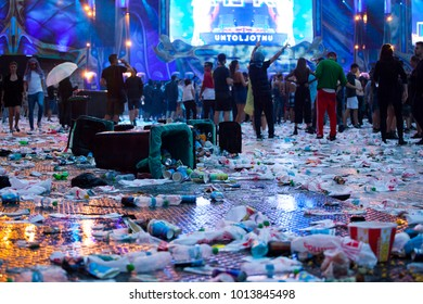 Cluj-Napoca, Romania - August 6, 2017:  Dancefloor full of plastic waste and food residues after four days of party, dancing people in the background at Untold Festival, Cluj-Napoca, Romania