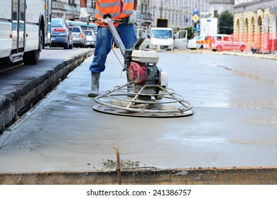 CLUJ-NAPOCA, ROMANIA - CIRCA JULY 2014: Construction worker finishes concrete slab with trowel machine by road upgrade. Road segments are partially closed for traffic on one of the main streets.