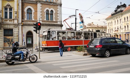 Cluj-Napoca, Romania - circa May, 2018: Young pedestrian woman, a tram, a bike and cars wait at the crossroads with traffic lights in the city.